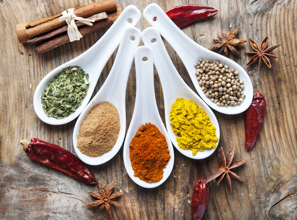 Top view on mixed dry colorful spices on wooden rustic table. Indian food and various oriental cooking ingredients background.